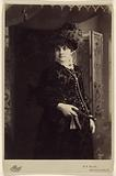 Unidentified woman in fine dress and hat, standing