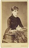 Unidentified young woman leaning on a carved box covered with fur