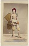 Unidentified boy wearing native costume with baskets on back and carrying a water jug and small basket, standing