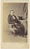 Unidentified man with moustache seated, a top hat on a nearby table