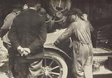 Men grouped around the hood of a car