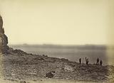 View of shore with ships on horizon and five figures standing on beach