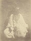 Portrait of a Native woman Sitting Against a wall