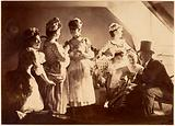 A Group of Six Costumed Women Posed in Interior with Top Hatted Gentlemen
