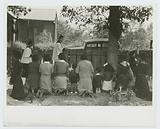 Negroes kneeling at graves of their relatives, and being blessed by Priest with Holy Water, New Roads, La