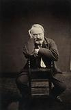 Victor Hugo from the front, seated astride a chair
