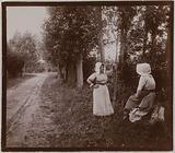 Two women chatting on the side of a tree-lined road, Amiens