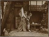 Couple of actors wearing Japanese costumes and playing pantomime, young woman holding a Japanese musical instrument: …