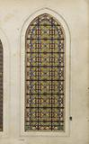 Stained glass window with decorative motifs: yellow background, red squares, blue quatrefoils, entourage with red …