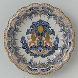 Bowl with scalloped edge. In the center a heraldic ornament.