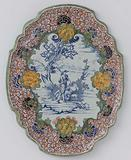 Plate, oval with scalloped edge with shepherd scene in blue, framed by a multicoloured flower border