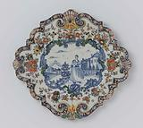 Plate, diamond-shaped with scalloped edge. Inside a multicoloured border a blue painted scene of a lady in a garden.