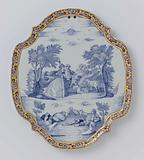 Plate, oval with scalloped edge with a shepherd's scene in blue within a multicoloured flower border