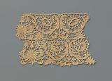 Strip of brown needle lace consisting of two strips sewn together with an imperial-like flower between acanthus leaves