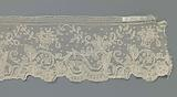 Strip bobbin lace with zigzag garland above an edge with s-scrolls