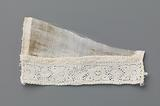 Strip of bobbin lace with stylized flower between two vertical lines and ovals on a triangular piece of linen batiste