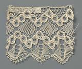 Strip of bobbin lace with diamonds between zigzag lines of openwork circles