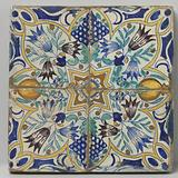 Four tiles that together form a star surrounded by tulips, bunches of grapes and pomegranates