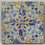 Four tiles that together form a star surrounded by lilies, tulips, bunches of grapes and pomegranates