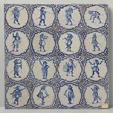 Field of sixteen tiles (4x4), each with a blue painted warrior, framed by a scalloped edge and meanders in the corners