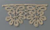 Strip bobbin lace with two scallops each formed by a seven-lobed flower between two oval leaves made with a bobbin …