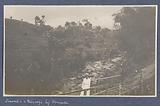 Two people on a bridge over a river near Wonosobo, in the background sawas