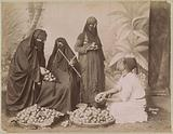 Portrait of an apple seller with veiled customers in Egypt