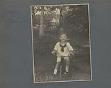Georges Bergsma on tricycle in garden on Sumatra