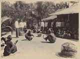 Men at a cockfight in a yard in the Dutch East Indies
