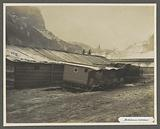 Barracks with parked ambulance sleds, one has a red cross