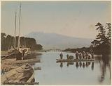 Mount Fuji seen over a water at Tagonoura, with people on a boat in the foreground