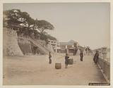 View of the city of Shimonoseki with people posing in the foreground and a boy with a cane