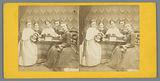 Girls around a table that may have a stereoscope and stereo photos