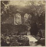 Landscape with an old overgrown bridge over a river in England
