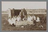 Group portrait of unknown men and women with tennis rackets and an amateur photographer on the right