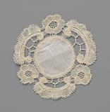 Bobbin lace dress or doily with C-volute and rosette flower