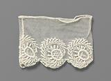 Lace embroidery cuff with sickle-shaped feathered branch that includes a circle with rays on one side
