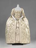 Overcoat with pleated Watteau of cream-coloured silk, with pleated silk strips, finished with narrow trim and light …