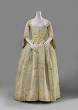 Overcoat with pleated Watteau of cream-coloured silk, embroidered in yellow with slender, widely measured flower and …