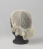 Frisian lace hat in fine knitting; the rim is wrinkled on the ball along the forehead.