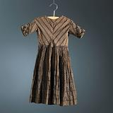 Cotton batiste dress, printed with a brown background in which a vertical striped pattern has been cut out.