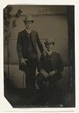 Portrait of two men, standing and sitting in a studio, with a paper on the back wall with the text Cayuga Lake Park (= …