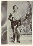 Studio portrait of a young Javanese woman in a sarong with a batik motif and a shirt with a check pattern