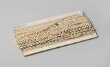 Trim of scalloped white lace with picots interlaced with an undulating shiny alternating rose green thread, on cardboard