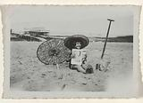 Portrait of a girl with a sun hat sitting on the beach (van Vinkeveen?)