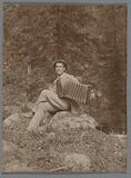 Man with accordion on tree stump in a forest
