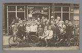 Group portrait of children in front of a grocery shop