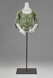 Straitjacket or lace body with white flowers on grass green ground, square neckline, half-length sleeves with 'manches …