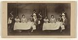 Theater group at the table, with two servants or waiters on either side