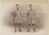 Two French men dressed in children's clothes with hoop and ball